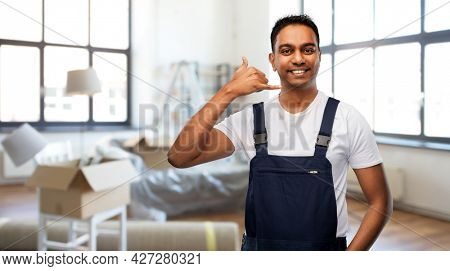 moving, repair and people concept - happy smiling indian worker, loader or repairman making phone call gesture over new home background