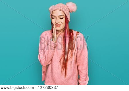 Young caucasian woman wearing casual clothes and wool cap touching mouth with hand with painful expression because of toothache or dental illness on teeth. dentist