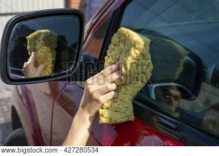 Little Girl Wash The Side Fender Of The Car With A Washcloth On A Sunny Day After A Flood
