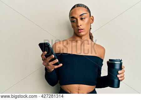 Hispanic transgender man wearing make up and long hair using smartphone and drinking a cup of coffee in shock face, looking skeptical and sarcastic, surprised with open mouth