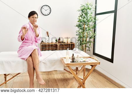 Beautiful caucasian woman wearing bathrobe at wellness spa disgusted expression, displeased and fearful doing disgust face because aversion reaction. with hands raised
