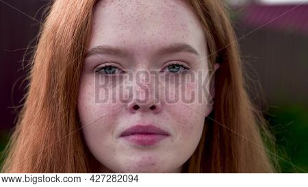 18 Year Old Red-haired Girl Sadly Looks At The Camera, Wiping Away Her Tears. Close-up