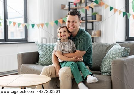 family, fatherhood and people concept - portrait of happy smiling father and little son sitting on sofa at home party