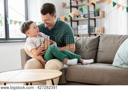 family, fatherhood and people concept - portrait of happy smiling father and little son hugging at home birthday party
