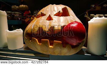 Standard Symbol Of Halloween, Jack Lantern. Scary Head Of Pumpkin Bites Red Apple.