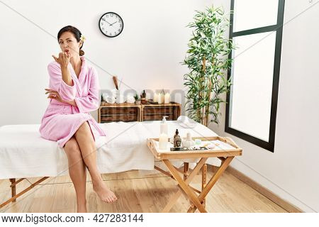 Beautiful caucasian woman wearing bathrobe at wellness spa looking at the camera blowing a kiss with hand on air being lovely and sexy. love expression.