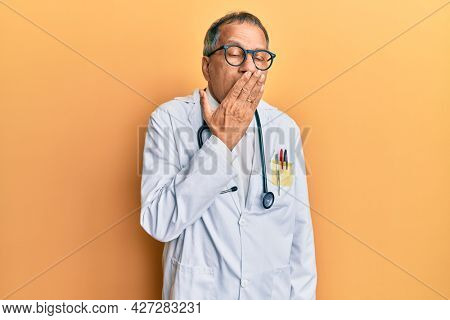 Middle age indian man wearing doctor coat and stethoscope bored yawning tired covering mouth with hand. restless and sleepiness.