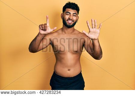 Arab man with beard wearing swimwear shirtless showing and pointing up with fingers number seven while smiling confident and happy.