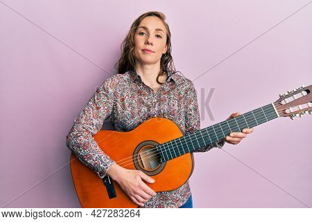 Young blonde woman playing classical guitar relaxed with serious expression on face. simple and natural looking at the camera.