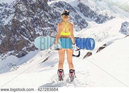 A Young Pretty Model Snowboarder With A Beautiful Figure In A Swimsuit Is Standing With Her Back And