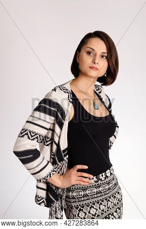Young Woman In Eco Style Clothes Posing In White Background. Portrait Of Young Woman In Aztec Style.