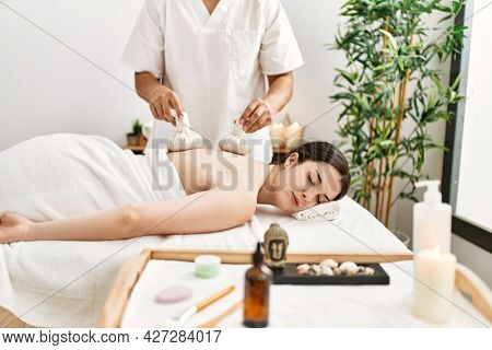 Young woman reciving herbal pouches thai massage at beauty center.