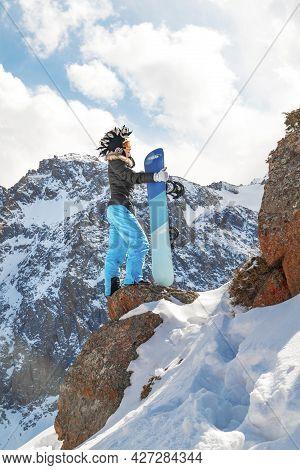 Freeride Snowboarder Woman In Mohawk Hat On Top Of Rock In Snowy Mountain. Copy Space, Vertical