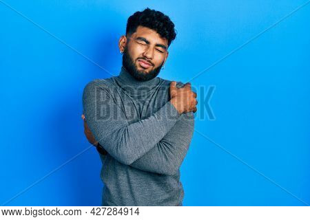 Arab man with beard wearing turtleneck sweater hugging oneself happy and positive, smiling confident. self love and self care