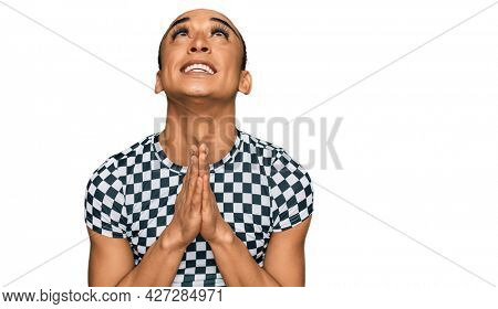 Hispanic transgender man wearing make up and long hair wearing modern clothes begging and praying with hands together with hope expression on face very emotional and worried. begging.