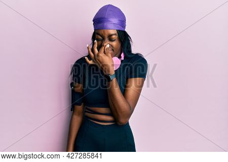 Young african american woman wearing gym clothes and using headphones smelling something stinky and disgusting, intolerable smell, holding breath with fingers on nose. bad smell
