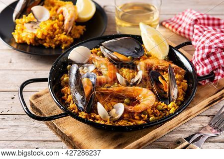 Traditional Spanish Seafood Paella On Wooden Table