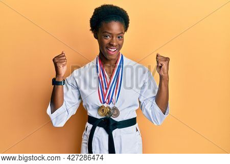 Young african american girl wearing karate kimono and black belt screaming proud, celebrating victory and success very excited with raised arms