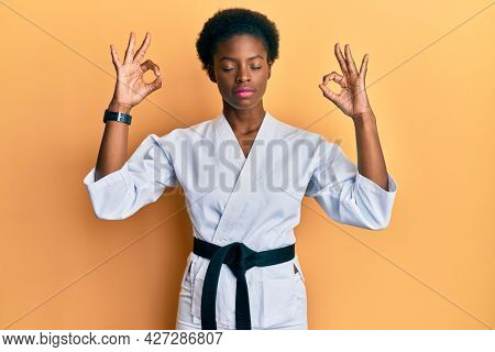 Young african american girl wearing karate kimono and black belt relax and smiling with eyes closed doing meditation gesture with fingers. yoga concept.
