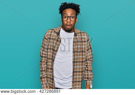 Young african american man with beard wearing casual clothes and glasses afraid and shocked with surprise and amazed expression, fear and excited face.