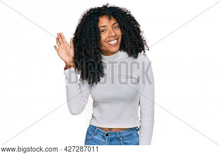 Young african american girl wearing casual clothes waiving saying hello happy and smiling, friendly welcome gesture