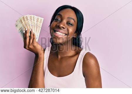 Young african american woman holding swedish krona banknotes looking positive and happy standing and smiling with a confident smile showing teeth