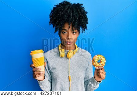 African american woman with afro hair eating doughnut and drinking coffee relaxed with serious expression on face. simple and natural looking at the camera.