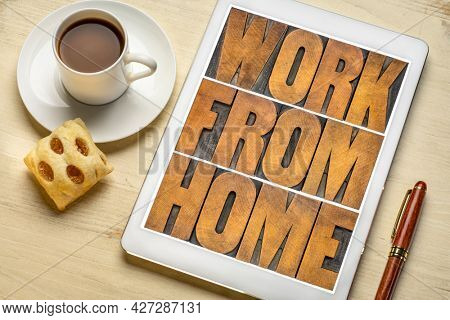work from home - word abstract in letterpress wood type on a digital tablet with coffee, telecommuting or self quarantine during covid-19 coronavirus pandemic