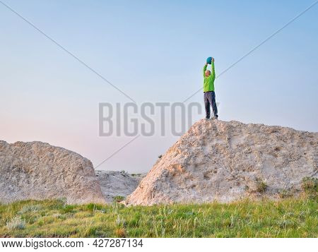 sunrise workout with a heavy slam ball - senior man exercise at a cliff in Pawnee National Grassland in Colorado