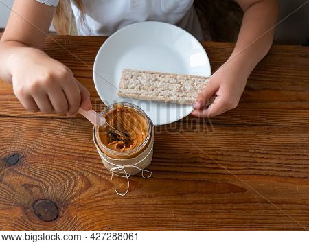 Child Eating Crispbread With Peanut Butter On Wooden Table Home Kitchen. School Girl With Bread Slic