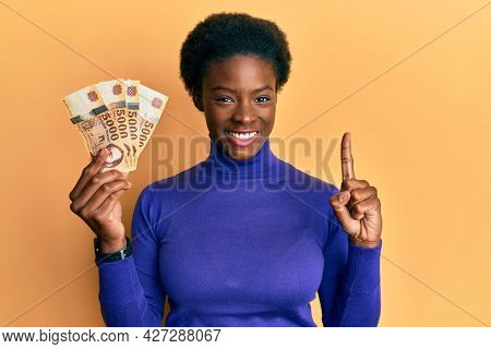 Young african american girl holding 5000 hungarian forint banknotes smiling with an idea or question pointing finger with happy face, number one