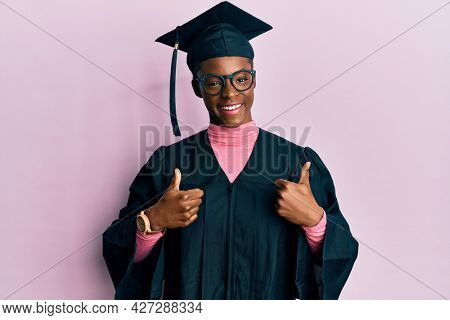 Young african american girl wearing graduation cap and ceremony robe success sign doing positive gesture with hand, thumbs up smiling and happy. cheerful expression and winner gesture.