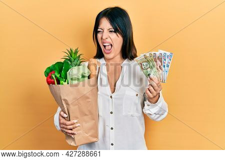 Young hispanic woman holding groceries bag and peruvian sol banknotes angry and mad screaming frustrated and furious, shouting with anger. rage and aggressive concept.