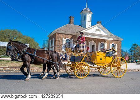Williamsburg, Virginia, USA: 31st March 2021; Tourists on a horse drawn buggy in Williamsburg, Virginia.