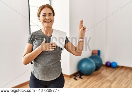 Middle age woman wearing sporty look training at the gym room smiling swearing with hand on chest and fingers up, making a loyalty promise oath