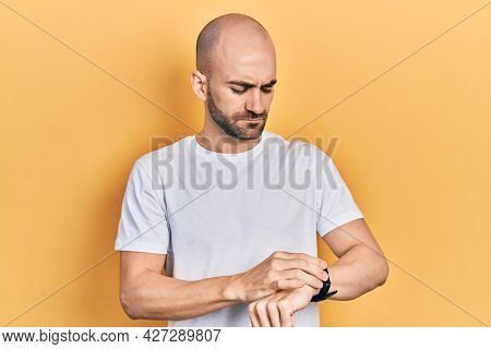 Young bald man wearing casual white t shirt checking the time on wrist watch, relaxed and confident