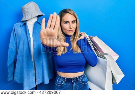 Young caucasian woman holding shopping bags with open hand doing stop sign with serious and confident expression, defense gesture