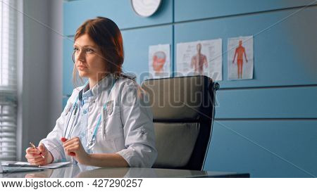 Young woman doctor talks to patient looking at sheets of papers and grey laptop display sitting in general practitioner office