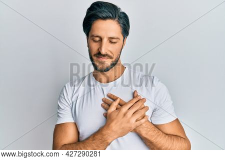 Young hispanic man wearing casual white t shirt smiling with hands on chest, eyes closed with grateful gesture on face. health concept.