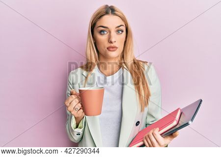 Young caucasian woman drinking a cup of coffee and holding laptop relaxed with serious expression on face. simple and natural looking at the camera.