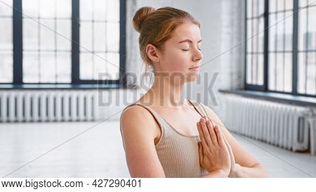 Concentrated young woman in comfortable tracksuit meditates with namaste mudra at training in spacious yoga studio