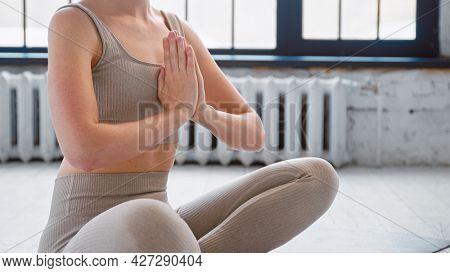 Slim woman in stylish sportswear sits in lotus pose holding hands in namaste mudra on floor in modern yoga studio closeup