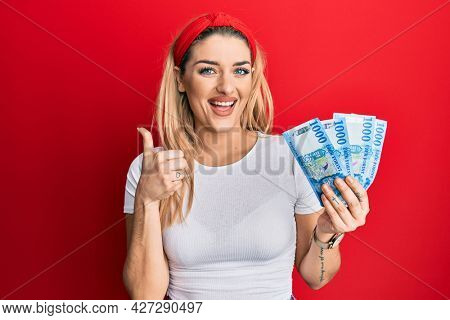Young caucasian woman holding 1000 hungarian forint banknotes smiling happy and positive, thumb up doing excellent and approval sign