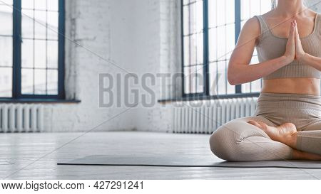 Slim woman in comfortable tracksuit meditates in yoga full lotus position sitting on floor in studio closeup space for design