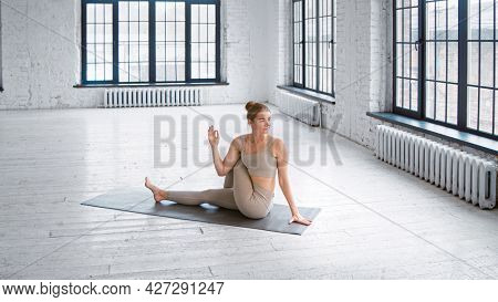 Flexible blonde lady in stylish light grey tracksuit does half lord of fishes pose sitting on mat in studio with large windows