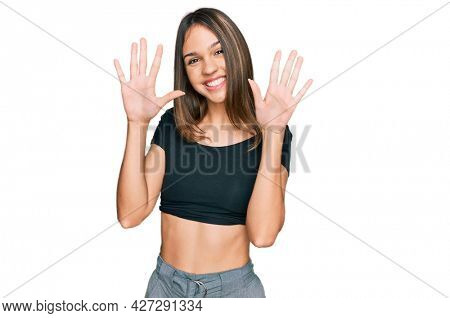 Young brunette woman wearing casual clothes showing and pointing up with fingers number ten while smiling confident and happy.