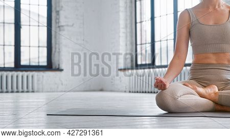 Barefoot sportswoman in beige tracksuit does breathing gymnastics in lotus pose on floor in studio close view space for design
