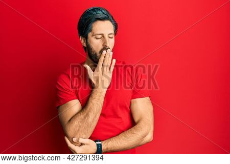Young hispanic man wearing casual red t shirt bored yawning tired covering mouth with hand. restless and sleepiness.