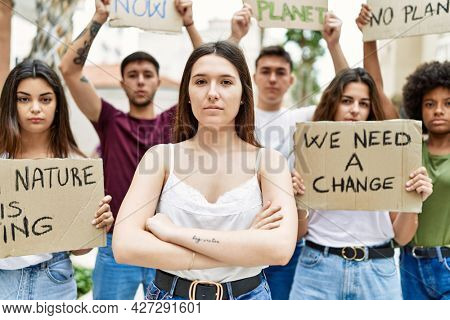 Young activist woman with arms crossed gesture standing with a group of protesters holding protest banner at the city.