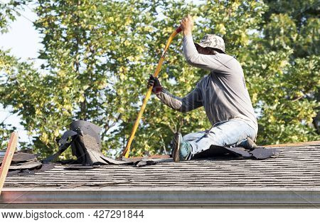 A Contractor Sitting On A Roof Removing The Old Shingles To Replacing Them With New Shingles On A Re